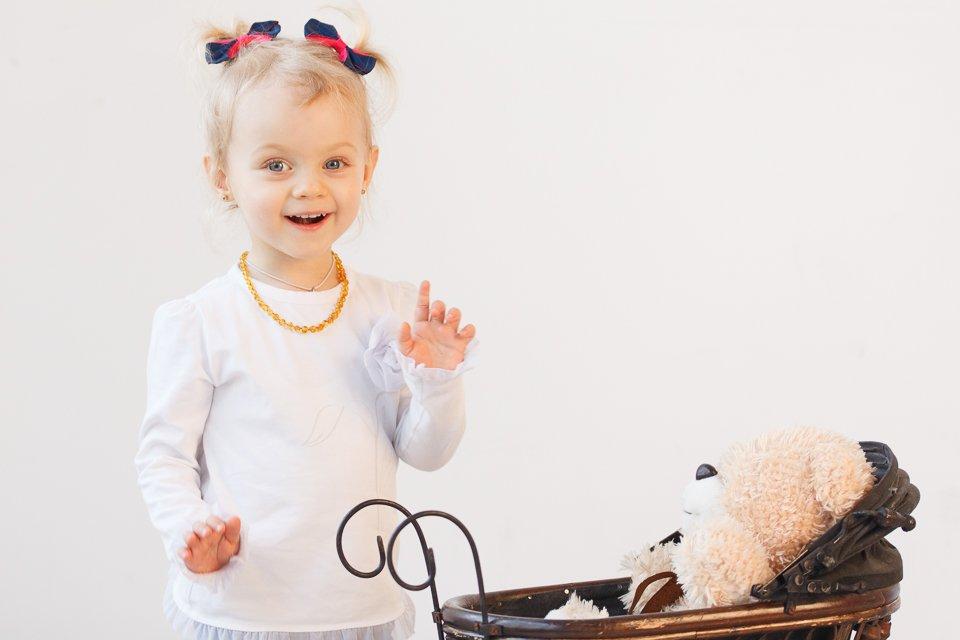 Ребенок играет с коляской в студии