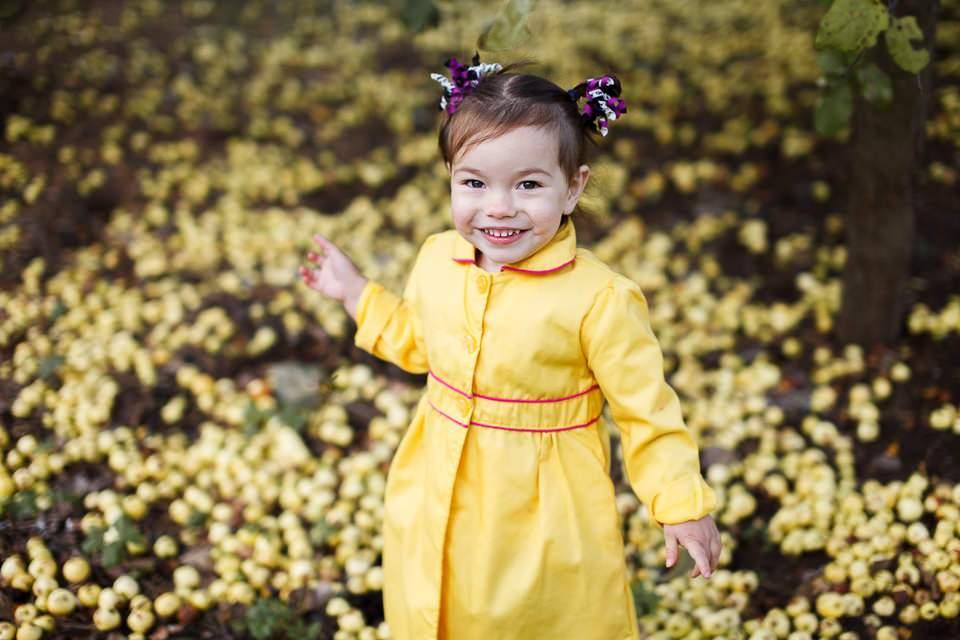 Фото девочки в желтом плаще среди желтых яблок