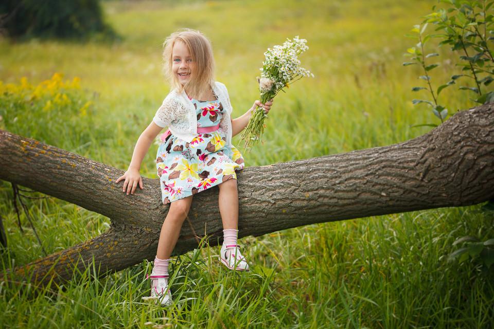 Фотосъемка девочки на дереве посреди поляны