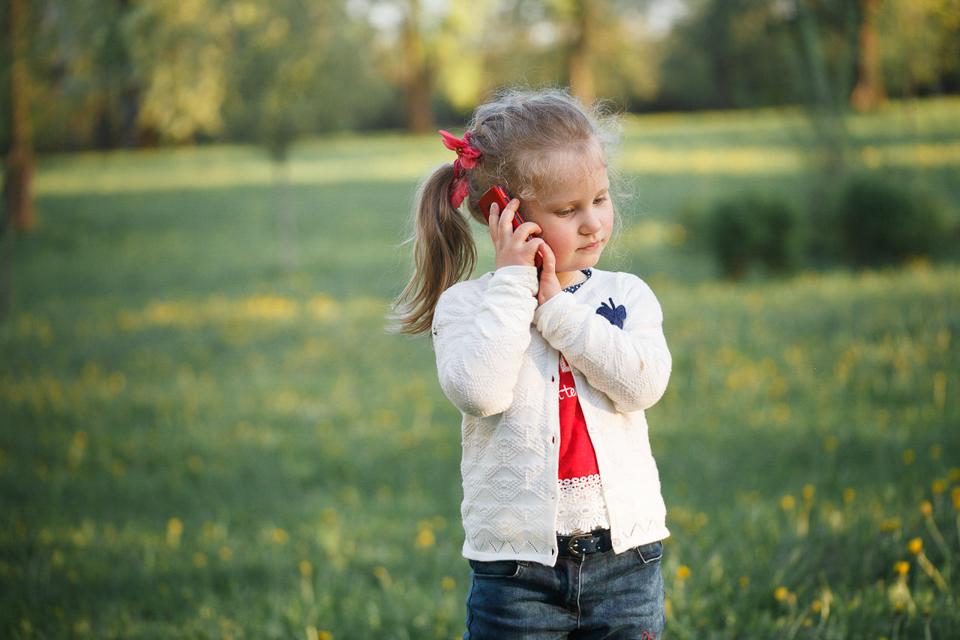 Фотография ребенка, играющего с телефоном