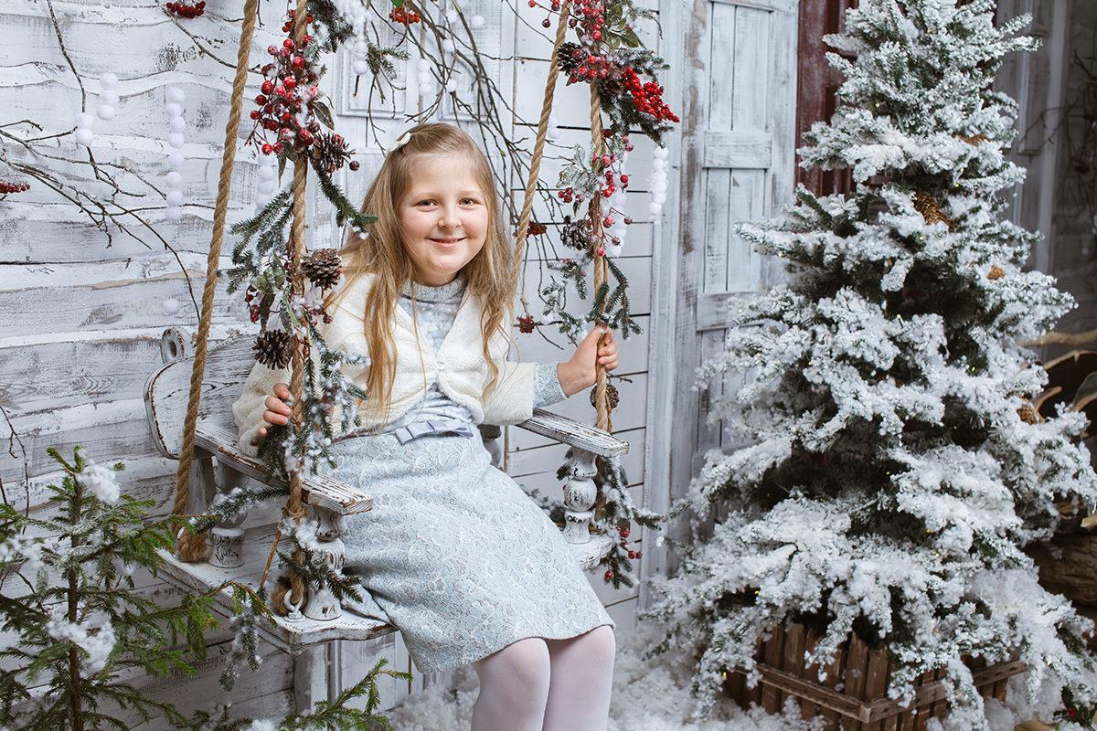Фото девочки на качелях в новогоднем интерьере в фотостудии в Минске