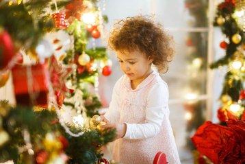 Ребёнок играет с новогодними игрушками
