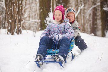 Дети катаются на санках в зимнем заснеженном лесу