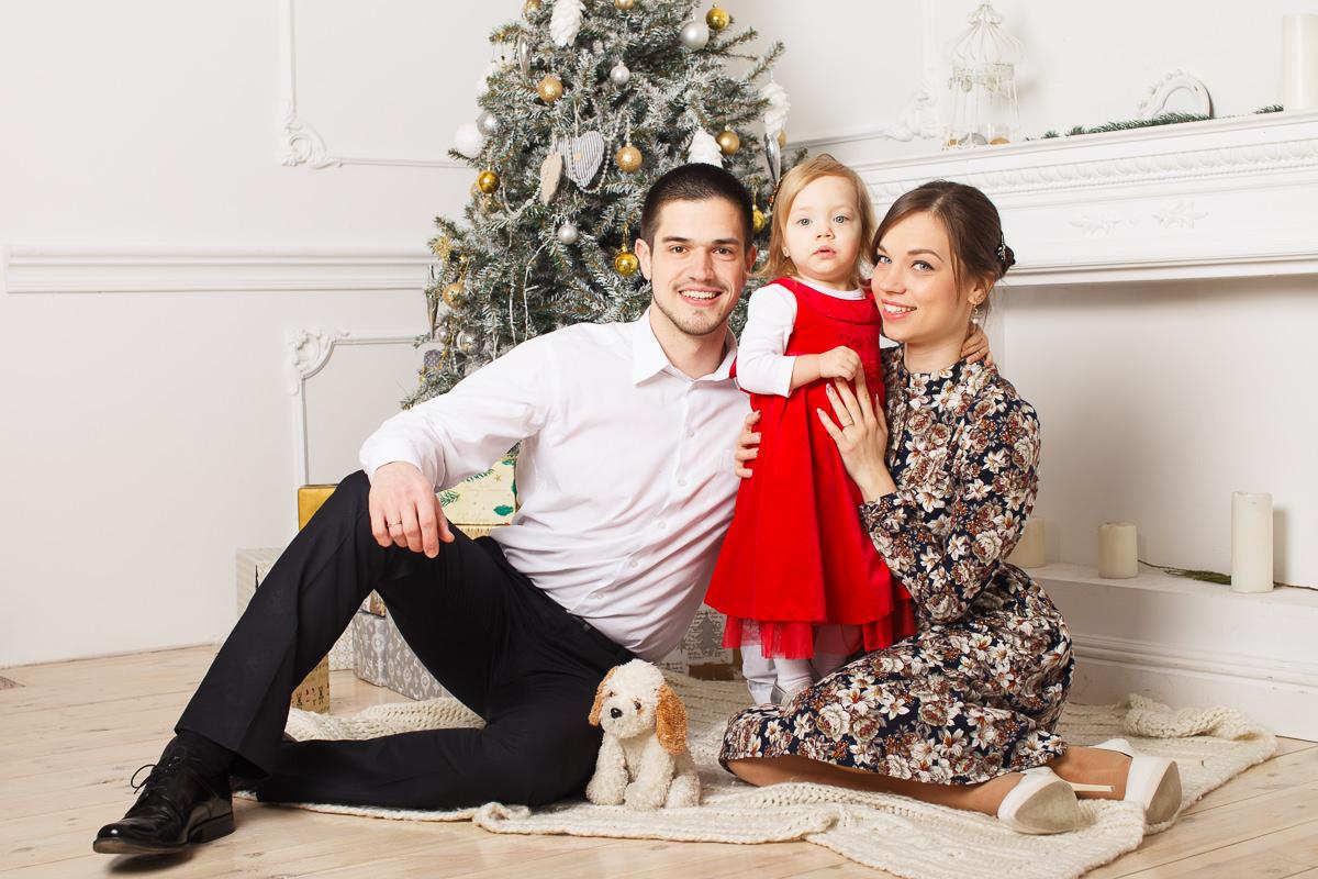 Фотография семьи с ребёнком возле новогодней ёлки