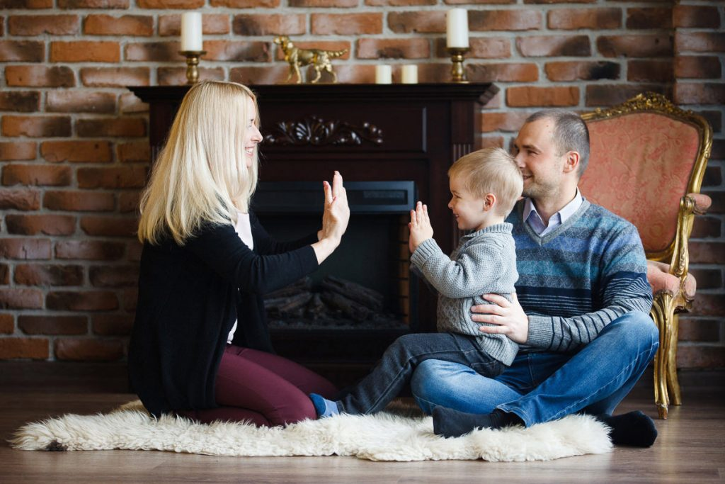 Фотография родителей с ребенком возле камина в студии