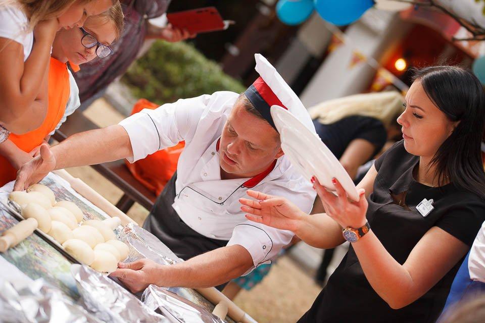 Фото повара, который учит детей готовить пиццу