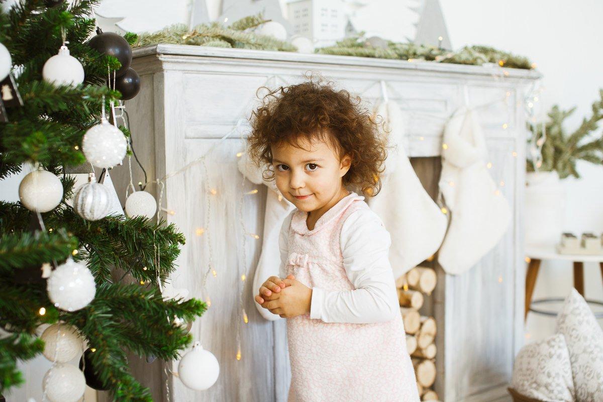Фотография девочки возле декоративного камина, украшенного гирляндами