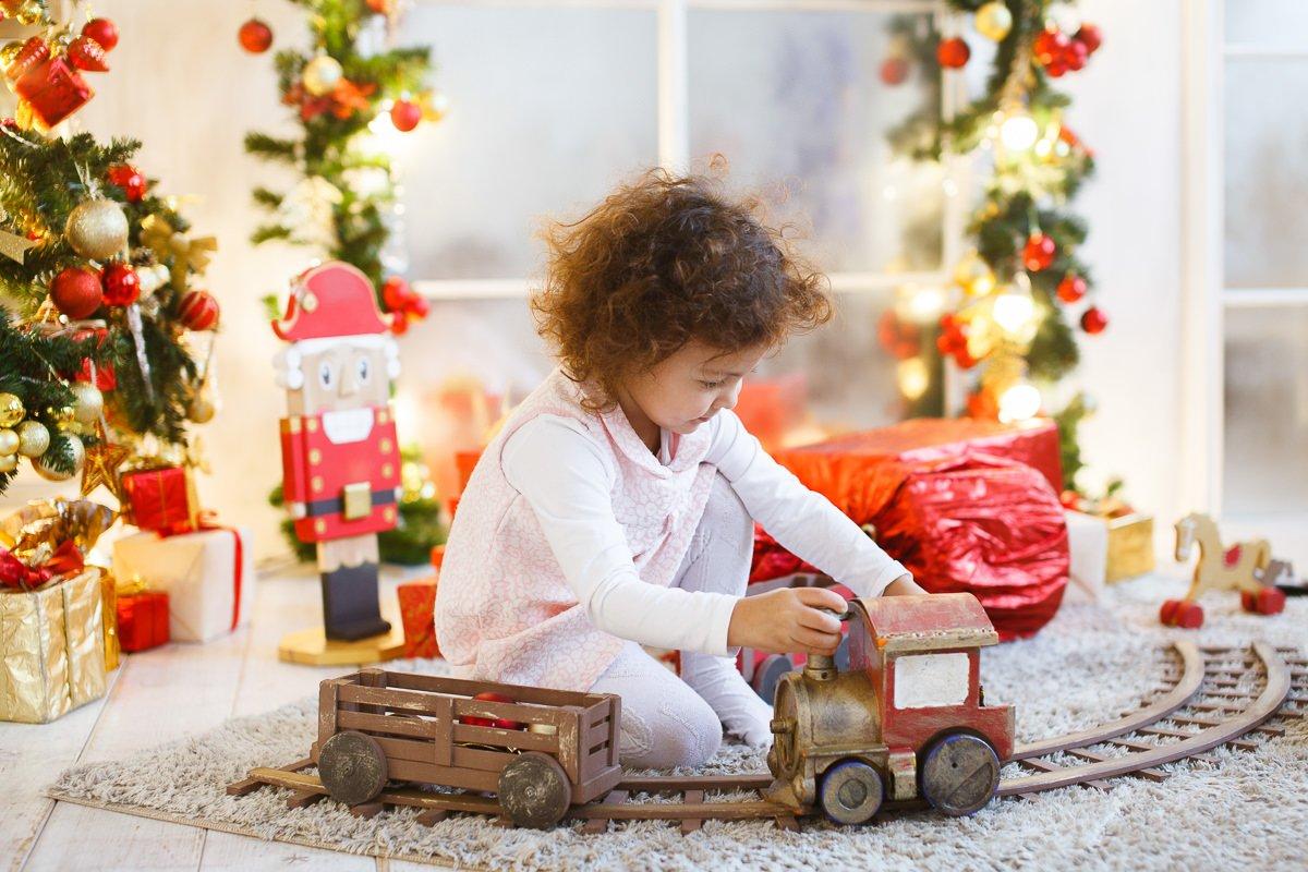 Девочка играет с игрушечной железной дорогой