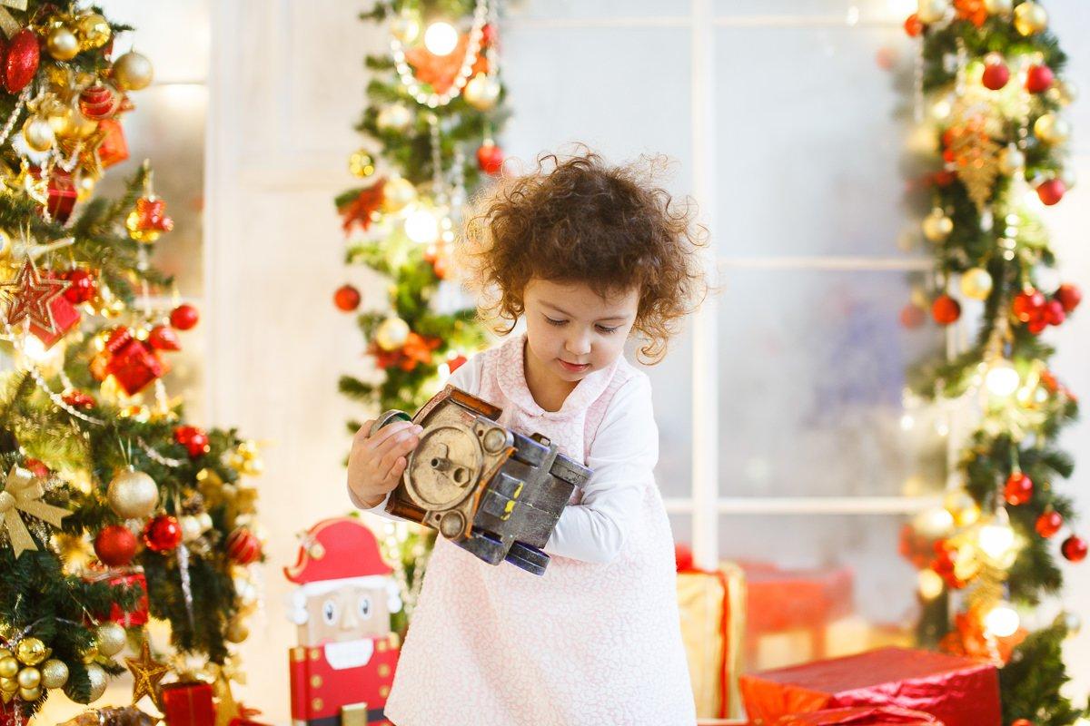 Фотография ребёнка среди новогодних декораций