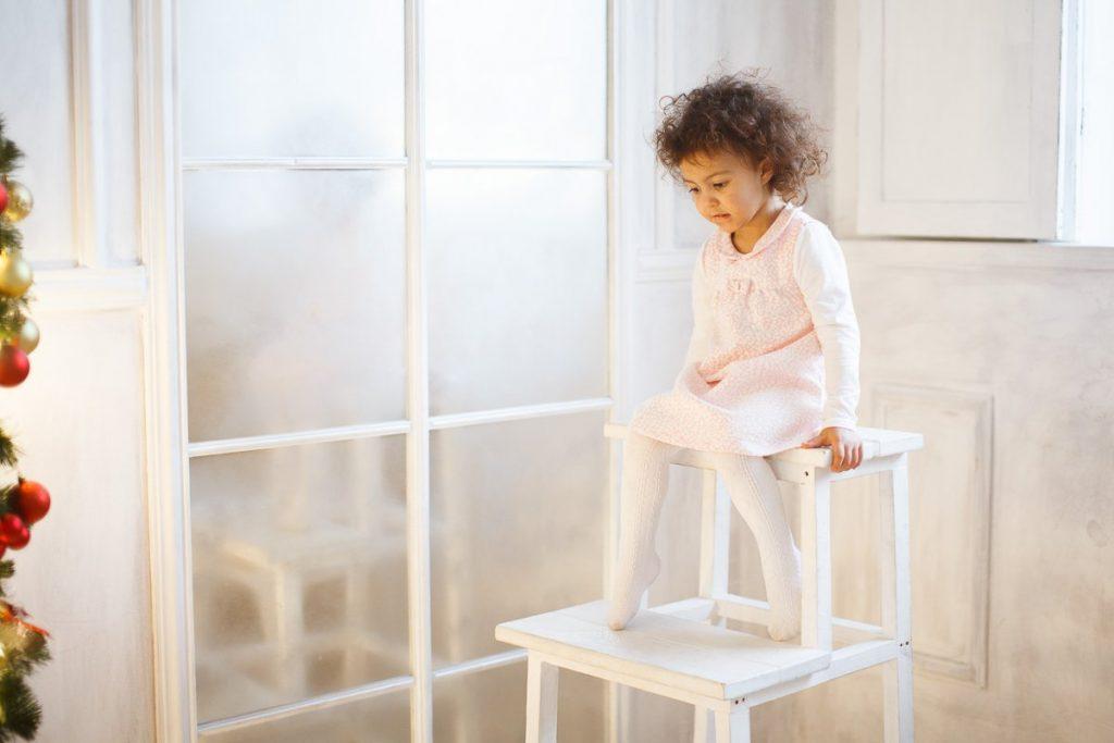 Детская фотосессия в студии - фотография ребенка на стуле