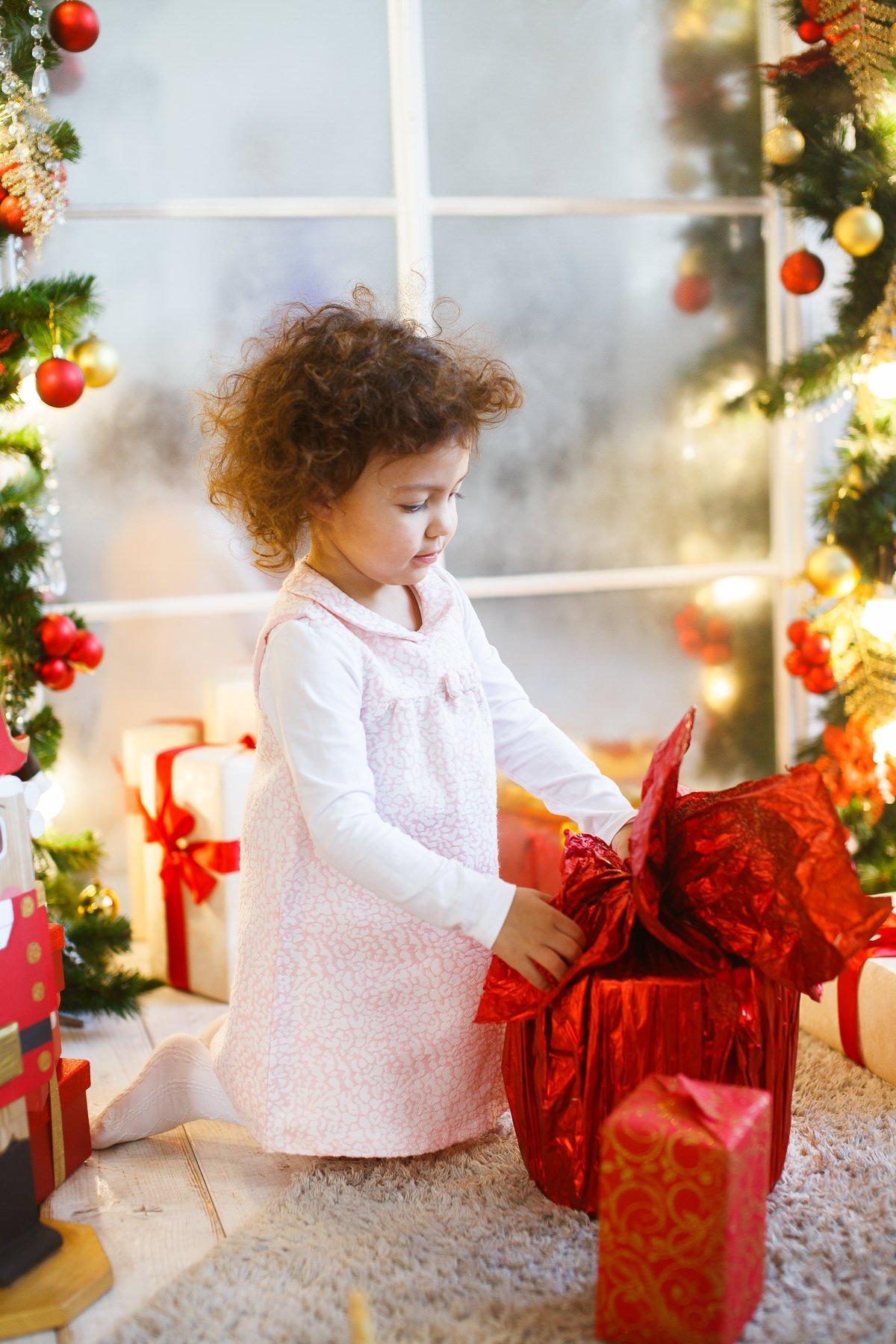 Фото ребёнка с большой подарочной коробкой возле ёлки