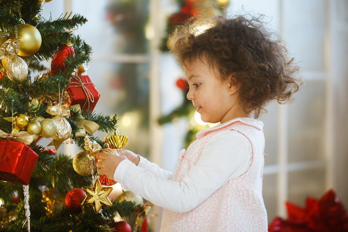 Фотография девочки возле нарядной новогодней ёлки