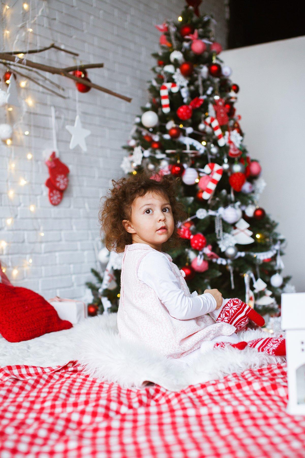 Новогодняя фотосессия - фото девочки на фоне красиво украшенной ёлки