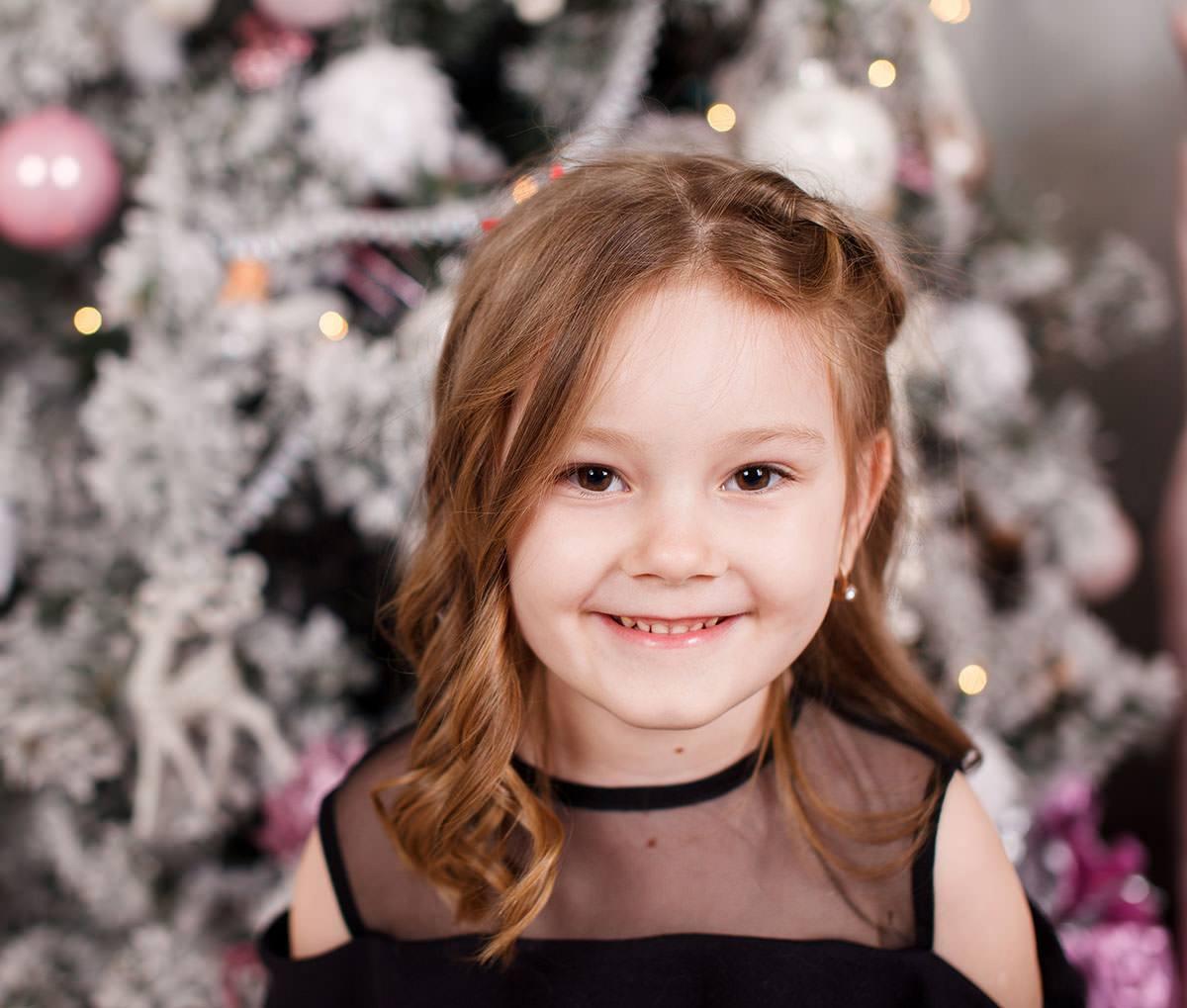 Портрет Варвары на фоне новогодней ёлки в интерьерной фотостудии