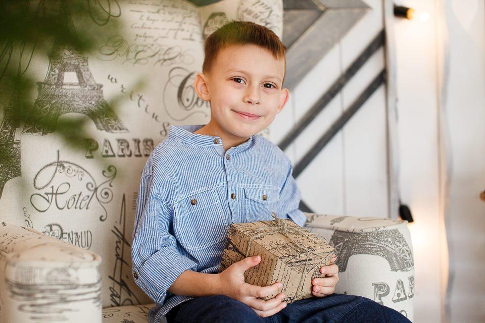 Портрет мальчика в кресле с подарком в руках
