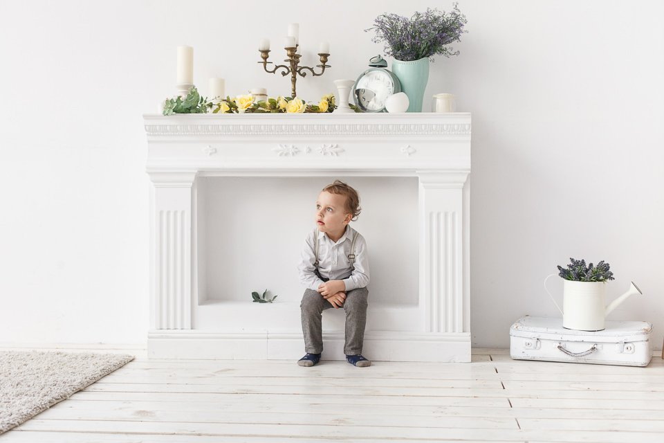 Фотография ребенка возле декоративного камина в интерьерной фотостудии